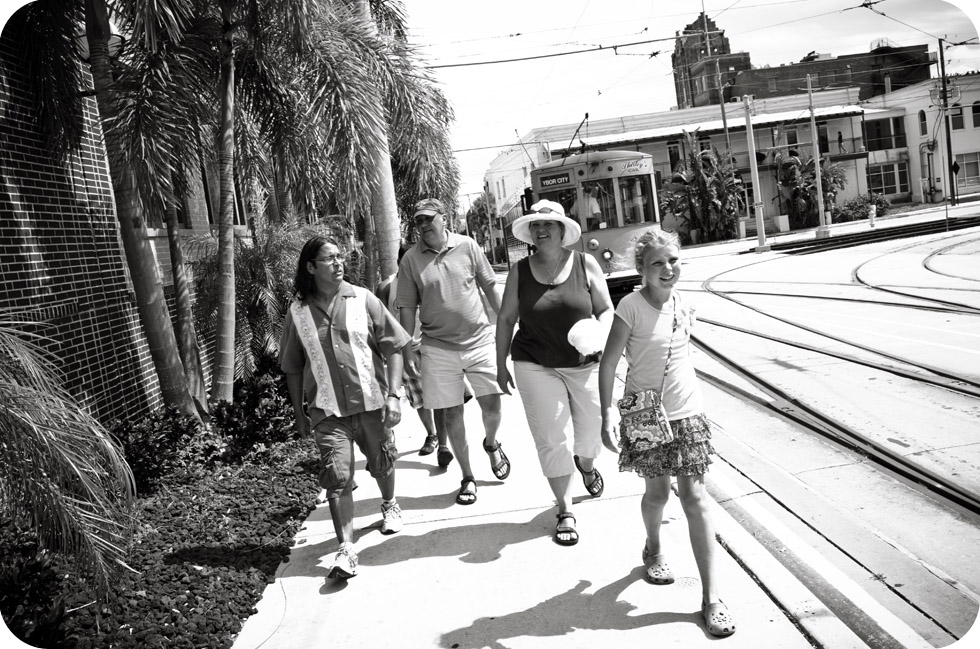 group of friends walking through Ybor City with trolley in background