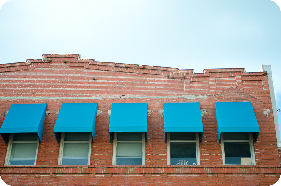 five second story windows with blue canopy coverings on brick building, 7th Ave Ybor City