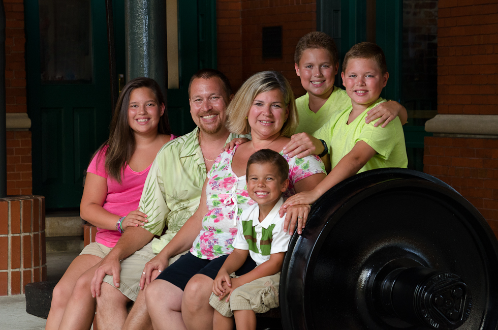 Family sitting on bench made of train wheels