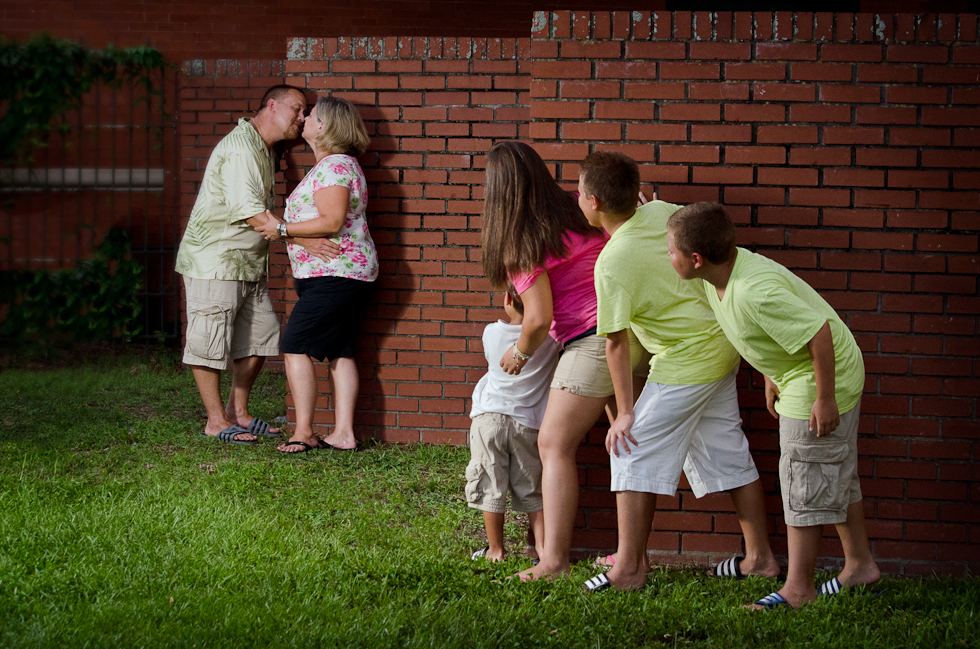 family portrait, mom and dad kiss as kids look on