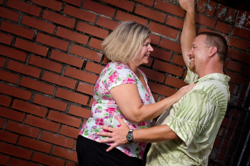 Couple's embrace in front of brick wall