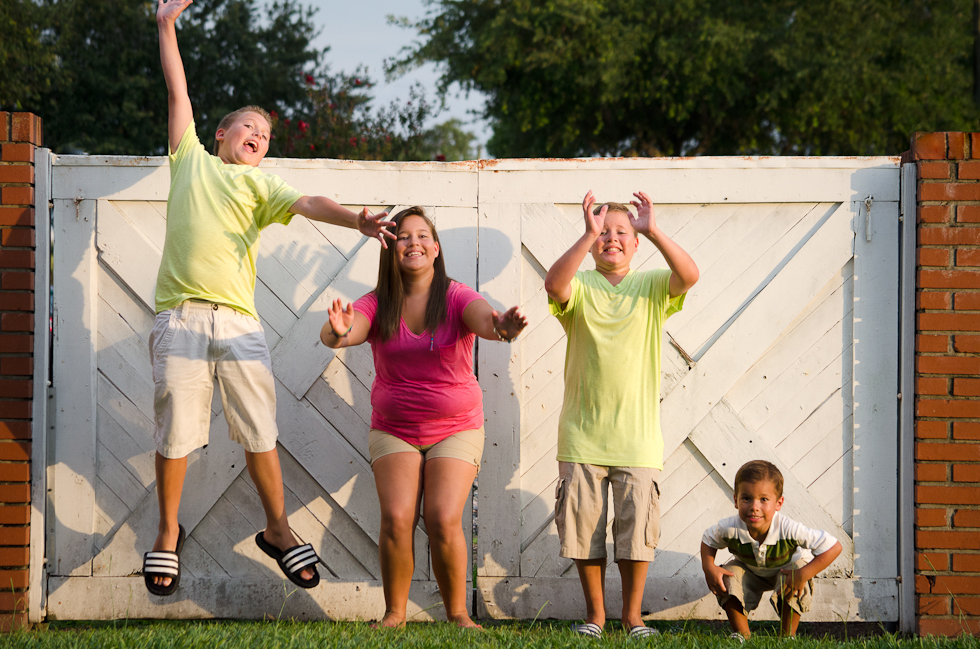 siblings jump in front of white gate