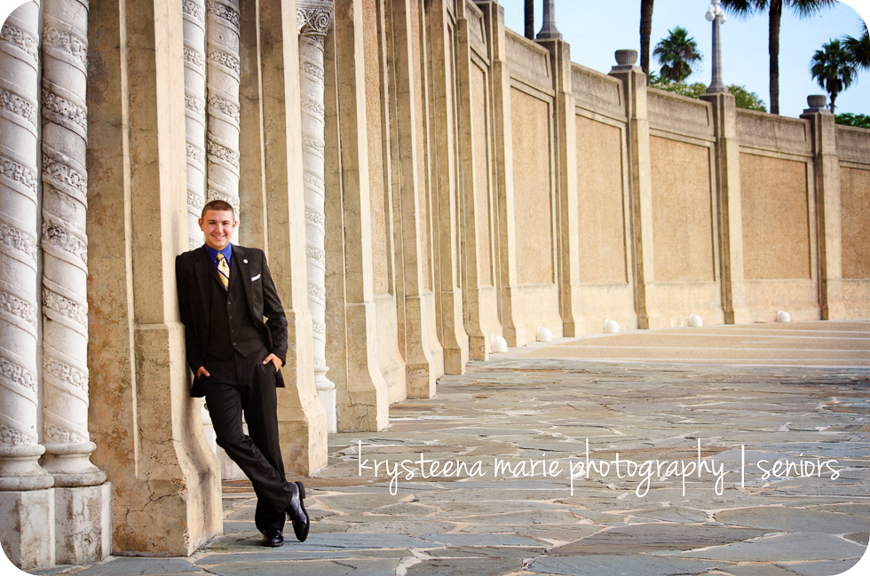 senior portrait guy in suit leaning against wall at lake