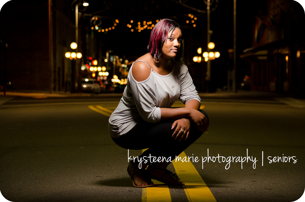 senior portrait girl  crouched in street 7th ave ybor night