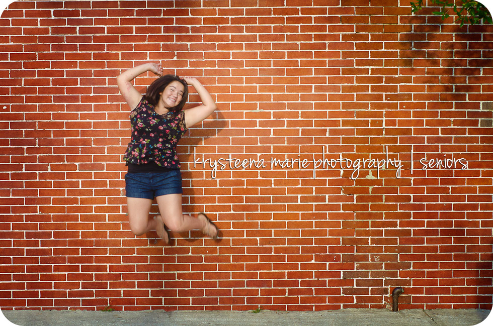 Senior portrait Chelsea jumping for joy brick wall