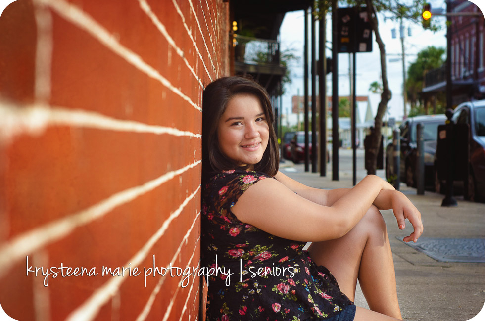 senior portrait Chelsea sitting against brick wall Ybor