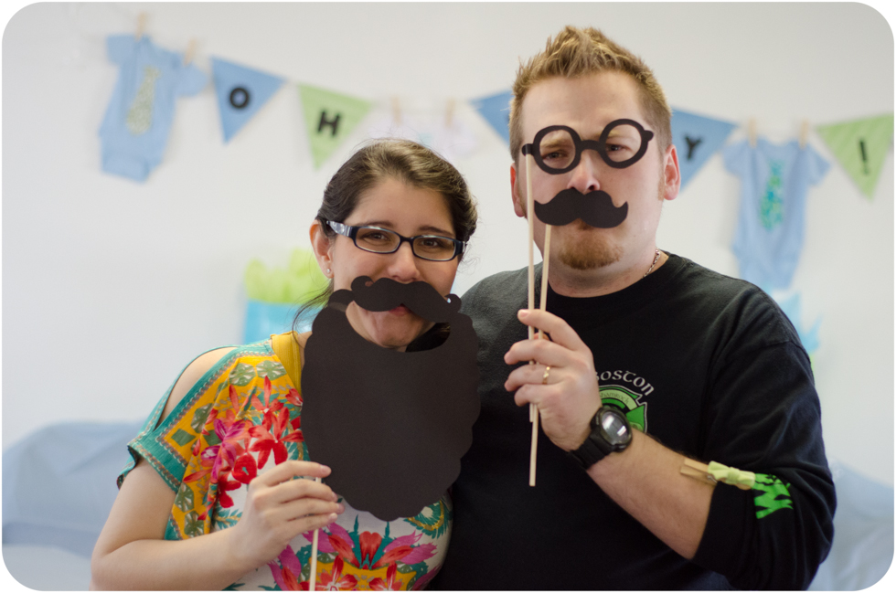 Kyle & Beth Wakefield Baby Shower pose with mustache props