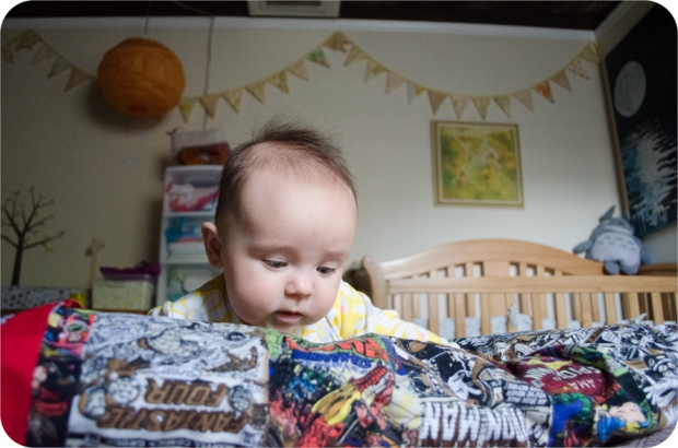 baby girl on Marvel Superhero background with plushTotoro, painting of moon, yellow bunting in background