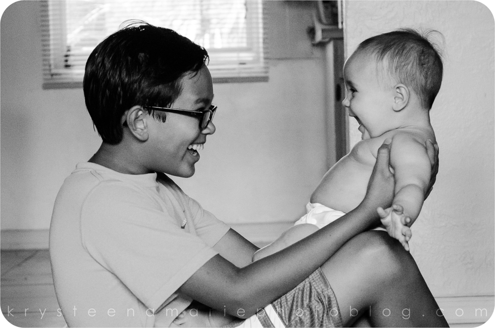 black and white image of brother holding baby sister big smiles