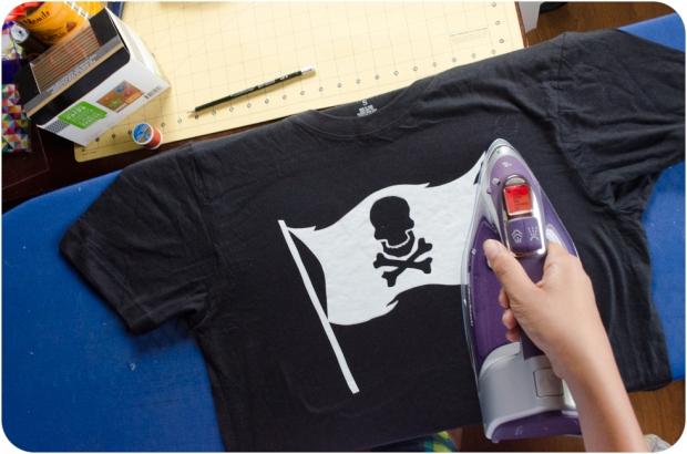 Ironing Jolly Roger pirate flag stencil onto black tee shirt for DIY bleach spray pirate shirt